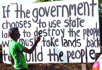 Activist Wayne Kublalsingh at a protest sign in Mon Desir, the site of the controversial multi-billion dollar highway.